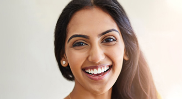 A beautiful model with white teeth smiling at the camera