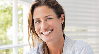 A middle aged woman with a beautiful smile looking at the camera
