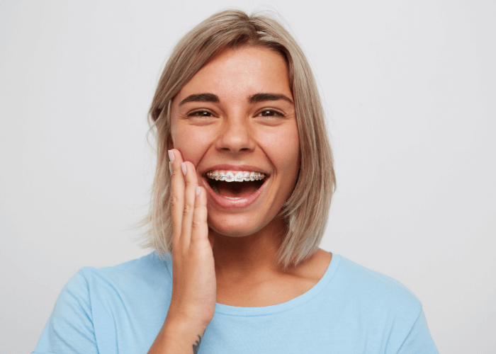 Woman wearing braces holding her face whilst smiling