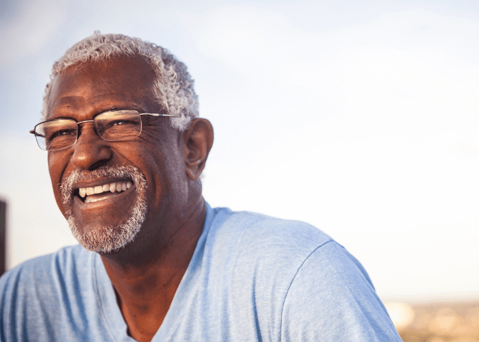 Old man with grey hair and glasses smiling