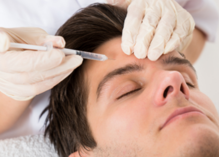 A woman injecting Botox into a mans forehead